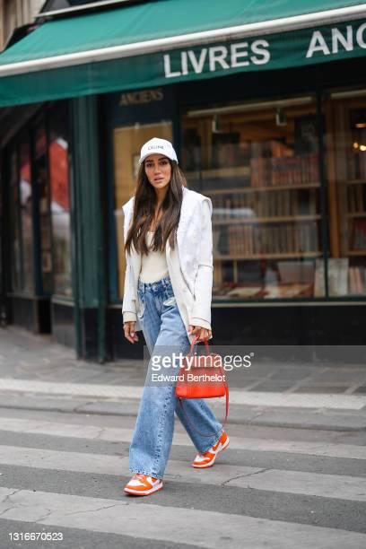 Tamara Kalinic wears a white Celine cap, a gold chain pendant necklace, a white latte ribs tank top, a white long Saint Laurent YSL blazer jacket, a...