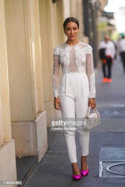 Tamara Kalinic wears a white lace mesh embroidered top white pants purple shoes a white Chanel bag outside Valentino during Paris Fashion Week Haute...