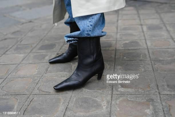 Tamara Kalinic wears a white long oversized Magda Butym coat, blue faded large oversized Margiela denim jeans pants, black shiny leather pointed...