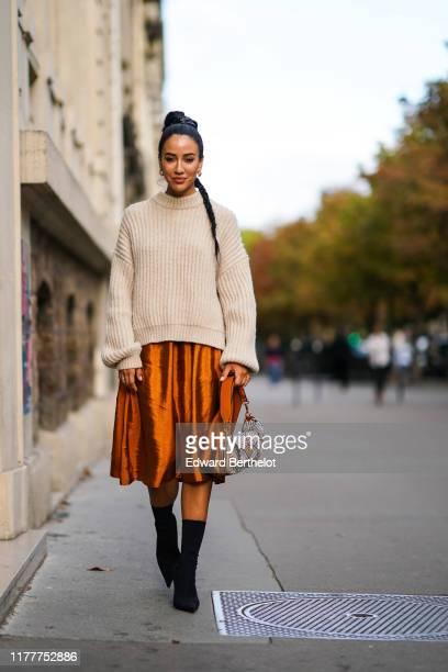 Tamara Kalinic wears a wool pullover, an orange shiny silky skirt, earrings, a Fendi bag, black high heeled boots, outside CDG Comme des Garçons,...