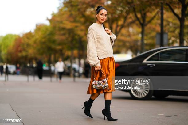 Tamara Kalinic wears a wool pullover an orange shiny silky skirt earrings a Fendi bag black high heeled boots outside CDG Comme des Garçons during...