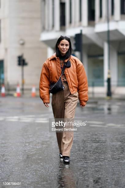Tamara Kalinic wears an orange leather bomber jacket, a crossbody fanny pack bag, beige pants, during London Fashion Week Fall Winter 2020 on...