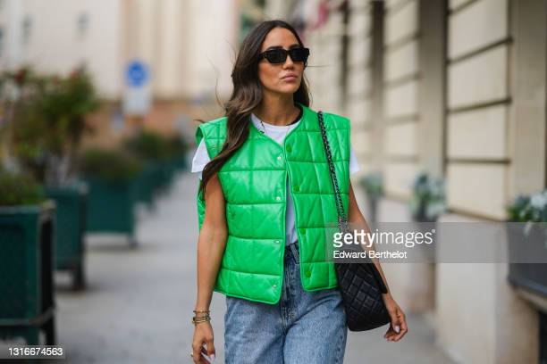 Tamara Kalinic wears black sunglasses, gold earrings, a gold chain pendant necklace, a black t-shirt, a white t-shirt with a slogan 'with me', a...