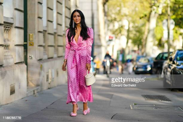 Tamara Kalinic wears earrings, bracelets, a lustrous pink with white polka dots long dress with long sleeves and a plunging neckline, a cream-color...
