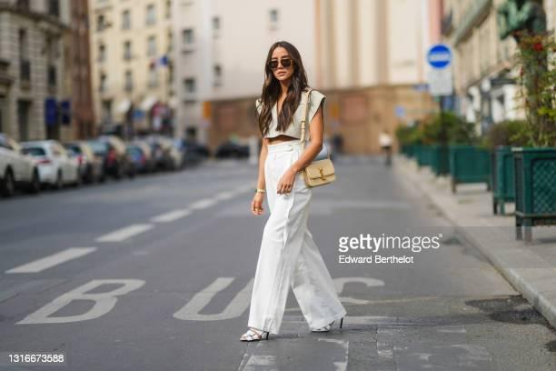 Tamara Kalinic wears gold Bottega Veneta sunglasses, a gold chain pendant necklace, a pale gray Jacquemus V-neck collar crop top with epaulets, white...