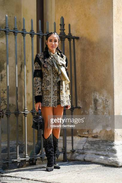 Tamara Kalinic wears long jacket dress with printed patterns a scarf a leather bag high boots outside the Etro show during Milan Fashion Week...