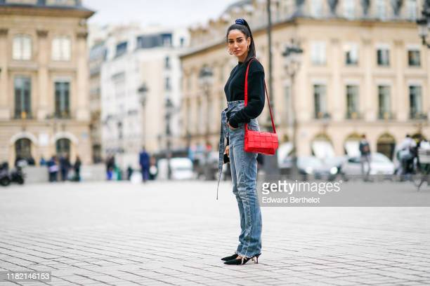 Tamara Kalinic wears Louis Vuitton earrings a black sweater with shoulder pads a red bag washedout blue denim highwaist ripped hem pants with an...