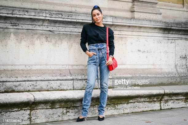Tamara Kalinic wears Louis Vuitton earrings, a black sweater with shoulder pads, a red bag, washed-out blue denim high-waist ripped hem pants with an...