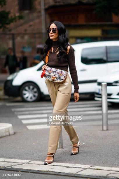 Tamara Kalinic wears sunglasses, a brown wool ripped turtleneck top, a Fendi bag, beige leather pants, outside the Fendi show during Milan Fashion...