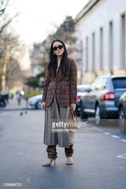 Tamara Kalinic wears sunglasses, a checked oversized blazer jacket, a pleated gray skirt, khaki pants, high heel shoes outside Schiaparelli, during...