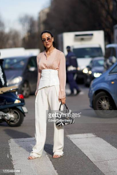 Tamara Kalinic wears sunglasses, a pink flowing shirt, a white corset, white flare pants, a Tod's balck and white zebra print bag, outside Tod's,...