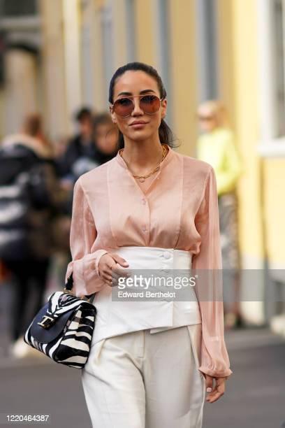 Tamara Kalinic wears sunglasses, a pink flowing shirt, a white corset, white flare pants, a Tod's balck and white zebra print bag, outside Tod's,...