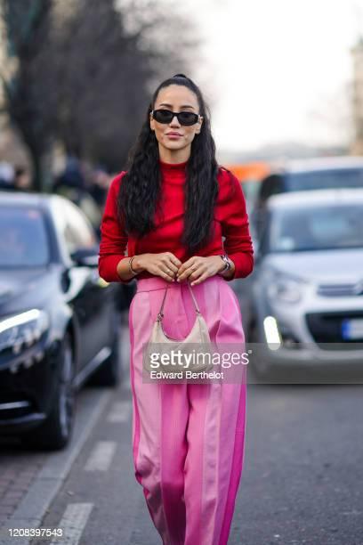 Tamara Kalinic wears sunglasses, a red top, a Prada bag, pink pants, outside BOSS, during Milan Fashion Week Fall/Winter 2020-2021 on February 23,...