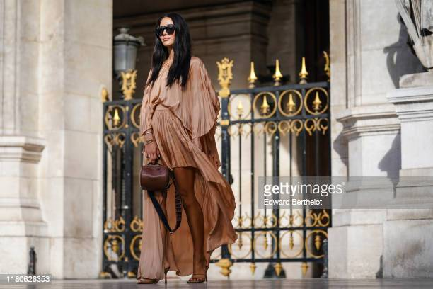 Tamara Kalinic wears sunglasses bracelets a lustrous light brown pleated highlow dress a brown Stella McCartney handbag brown heeled mules outside...
