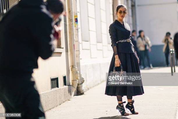 Tamara Kalinic wears sunglasses earrings a hair brooch a black pleated dress a Lady Dior bag with purple printed features poses in front of...