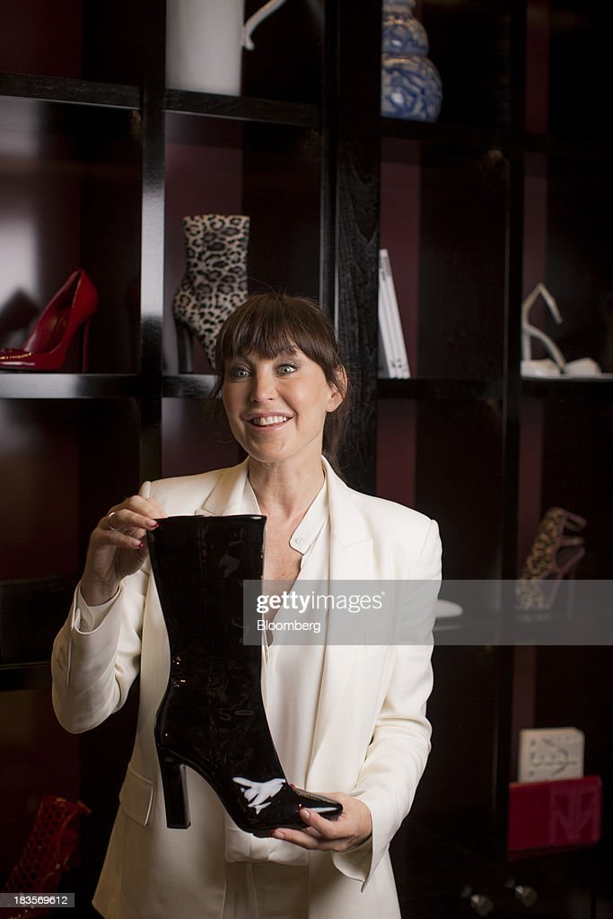 Tamara Mellon, president of TM Enterprises, holds a woman's black leather boot as she poses for a photograph in London, U.K., on Monday, Oct. 7, 2013. This autumn, Mellon, is launching her own line of clothes and shoes. Photographer: Jason Alden/Bloomberg via Getty Images