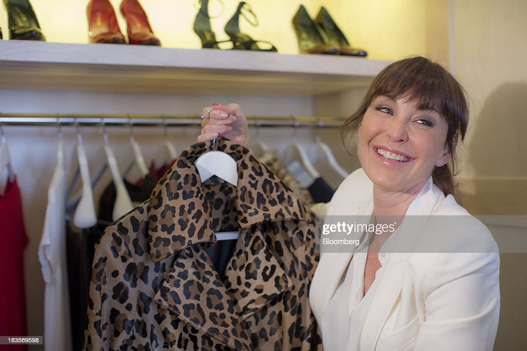 Tamara Mellon, president of TM Enterprises, poses for a photograph with a item of clothing from her new range in London, U.K., on Monday, Oct. 7, 2013. This autumn, Mellon, is launching her own line of clothes and shoes. Photographer: Jason Alden/Bloomberg via Getty Images