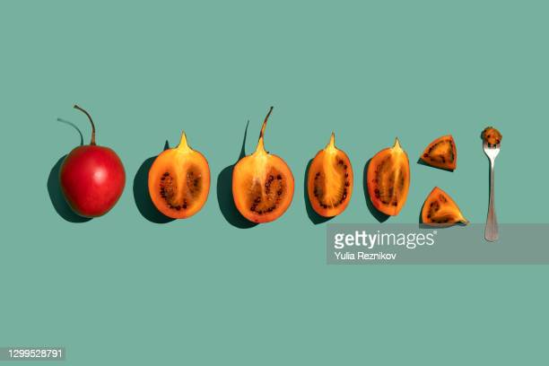 tamarillo (solanum betaceum) fruit on the green background - greenpeace stock pictures, royalty-free photos & images