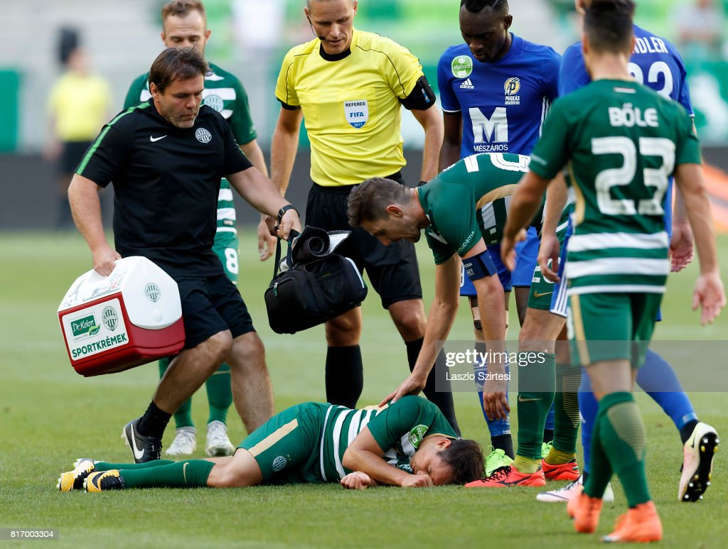 Tamas Hajnal (L) of Ferencvarosi TC lays unconscious on the ground among players during the Hungarian OTP Bank Liga match between Ferencvarosi TC and Puskas Akademia FC at Groupama Arena on July 16, 2017 in Budapest, Hungary.