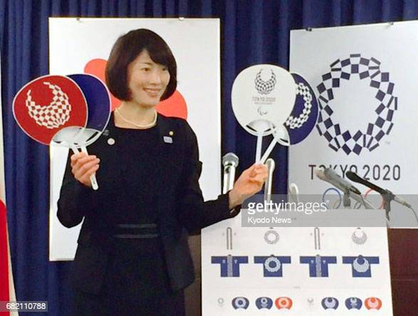 Tamayo Marukawa minister for the Olympics and Paralympics unveils paper fans promoting the 2020 Tokyo games at the Cabinet Office in Tokyo on May 12...
