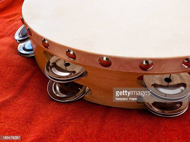 Tambourine on orange fabric.