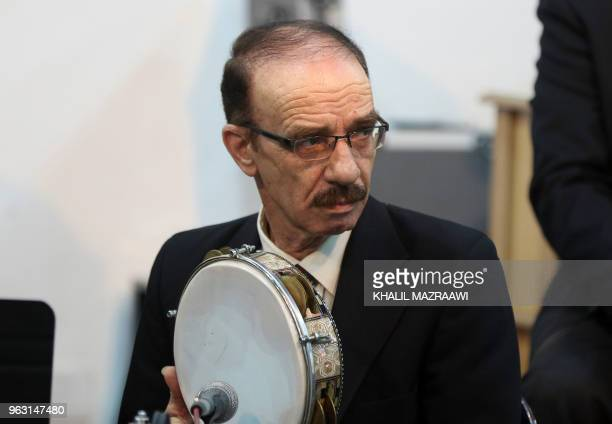 Tambourine player Ahmad Kamel performs with the Beit alRowwad ensemble during a concert at Hussein Cultural Center in Amman on March 13 2018 Beit...