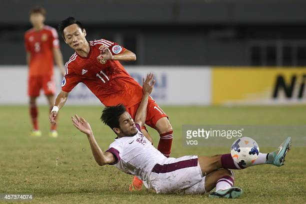 Tameem Mohammed E S Almuhaza of Qatar and Tang Shi of China battle for the ball during the AFC U19 Championship quarterfinal match between Qatar and...