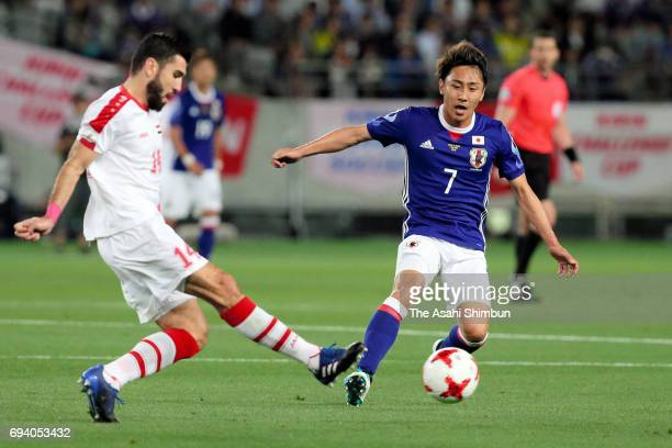 Tamer Hag Mohamad of Syria and Shu Kurata of Japan compete for the ball during the international friendly match between Japan and Syria at Tokyo...
