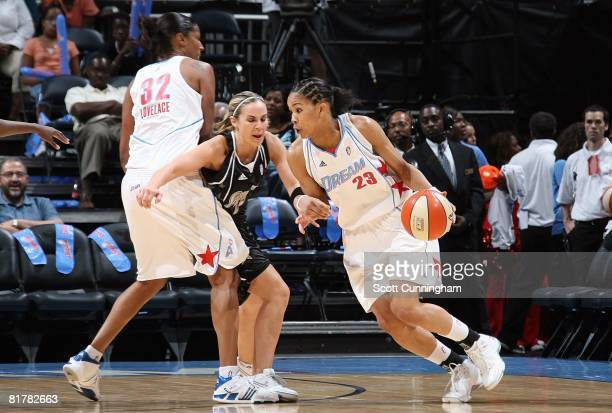 Tamera Young of the Atlanta Dream drives around the pick against Becky Hammon of the San Antonio Silver Stars during the WNBA game on June 18 2008 at...