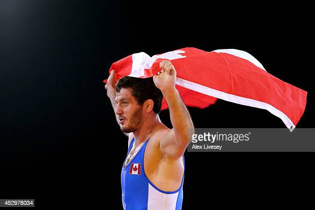 Tamerlan Tagziev of Canada celebrates winning the gold medal in the Men's FS 86 kg at Scottish Exhibition and Conference Centre during day eight of...