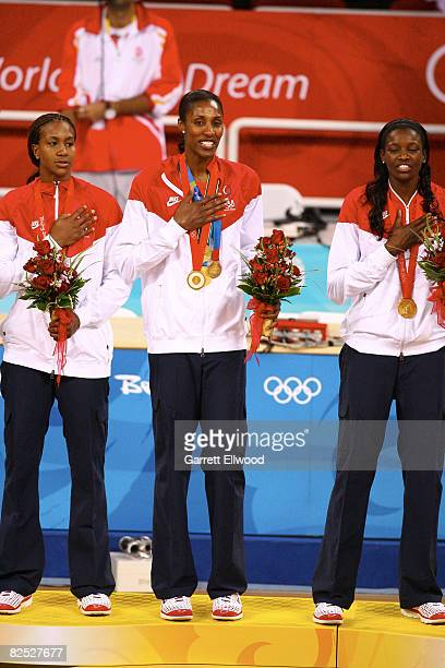 Tamika Catchings, Lisa Leslie and DeLisha Milton-Jones of the U.S. Women's Senior National Team celebrate after winning the gold medal against...