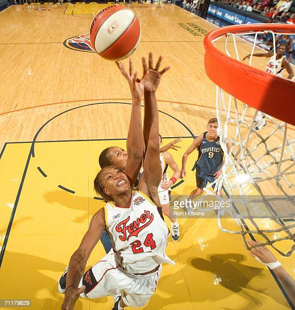 Tamika Catchings of the Indiana Fever battles a Seattle Storm defender on June 11 2006 at Conseco Fieldhouse in Indianapolis Indiana The Fever...