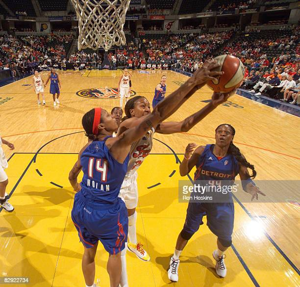 Tamika Catchings of the Indiana Fever battles Deanna Nolan and Taj McWilliamsFranklin of the Detroit Shock in Game One of the Eastern Conference...