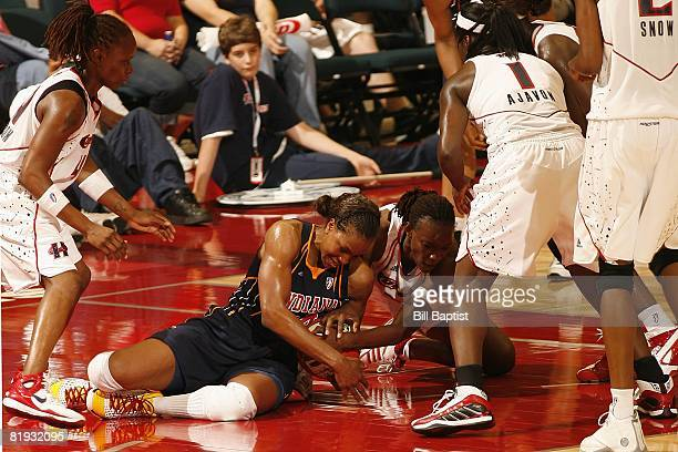 Tamika Catchings of the Indiana Fever battles for the loose ball against Shannon Johnson of the Houston Comets during the game at Reliant Arena on...