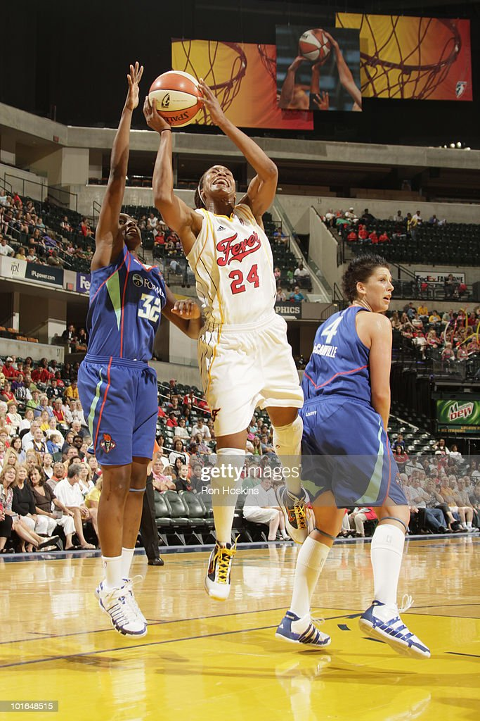Tamika Catchings #24 of the Indiana Fever battles Kalana Greene #32 and Janel McCarville #4 of the New York Liberty at Conseco Fieldhouse on June 5, 2010 in Indianapolis, Indiana.