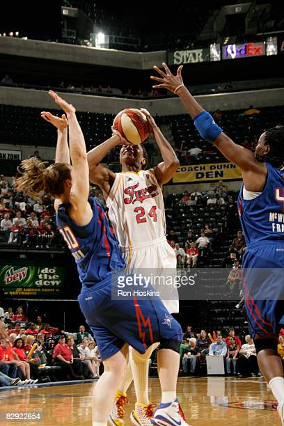 Tamika Catchings of the Indiana Fever battles Katie Smith and Taj McWilliamsFranklin of the Detroit Shock in Game One of the Eastern Conference...