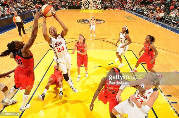 Tamika Catchings of the Indiana Fever battles Nicky Anosike of the Washington Mystics at Conseco Fieldhouse on July 9 2011 in Indianapolis Indiana...