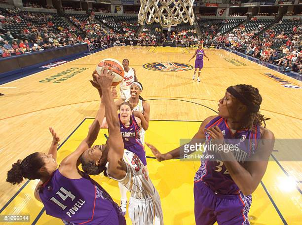 Tamika Catchings of the Indiana Fever battles Nicole Powell and Rebekkah Brunson of the Sacramento Monarchs at Conseco Fieldhouse June 24 2008 in...