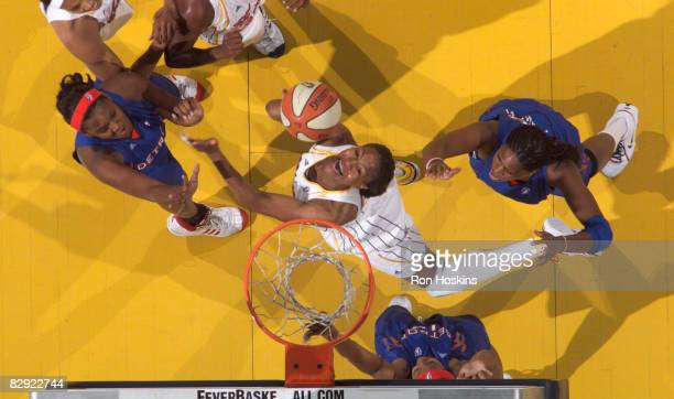 Tamika Catchings of the Indiana Fever battles Taj McWilliamsFranklin and Kara Braxton of the Detroit Shock in Game One of the Eastern Conference...