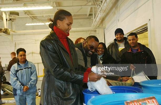 Tamika Catchings of the Indiana Fever delivers canned goods with help from volunteers November 25 2003 at Gleaners Food Bank in Indianapolis Indiana...