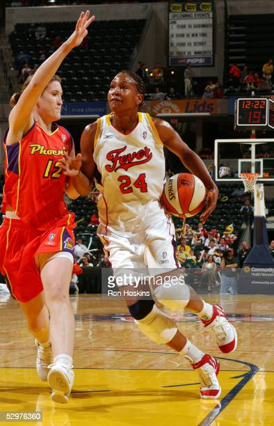 Tamika Catchings of the Indiana Fever drives on Belinda Snell of the Phoenix Mercury on May 24 2005 at Conseco Fieldhouse in Indianapolis Indiana...