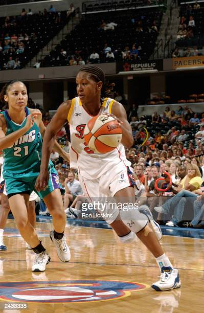 Tamika Catchings of the Indiana Fever drives past Allison Feaster of the Charlotte Sting during the game on August 16 2003 at Conseco Fieldhouse in...