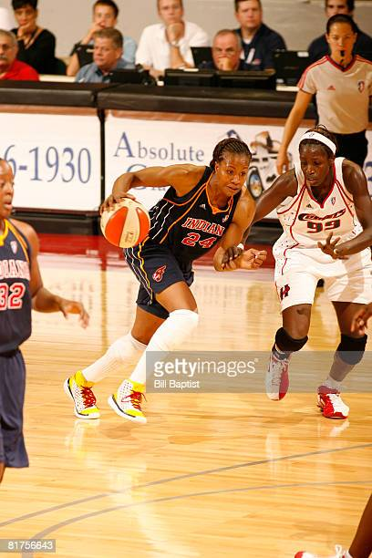 Tamika Catchings of the Indiana Fever drives the ball past Hamchetou Maiga-Ba of the Houston Comets at Reliant Arena on June 28, 2008 in Houston,...