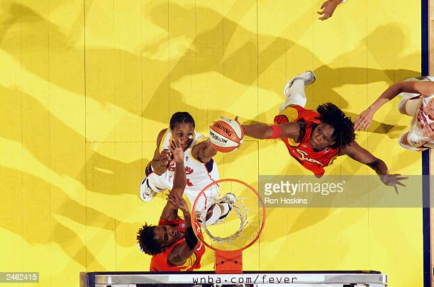 Tamika Catchings of the Indiana Fever fights for a rebound with Taj McWilliamsFranklin and Wendy Palmer of the Connecticut Sun during the game at...