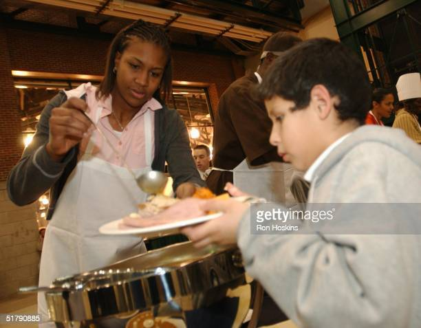 Tamika Catchings of the Indiana Fever serves gravy during the Austin Croshere 'Come To Our House' Thanksgiving Dinner at Conseco Fieldhouse on...