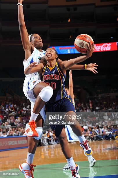 Tamika Catchings of the Indiana Fever shoots as Taj McWilliamsFranklin of the New York Liberty defends on July 18 2010 at Madison Square Garden in...