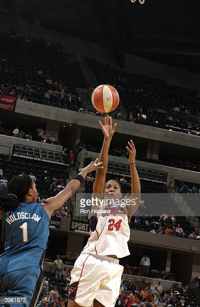 Tamika Catchings of the Indiana Fever shoots over Chamique Holdsclaw of the Washington Mystsics during the WNBA game at Conseco Fieldhouse on May 31...