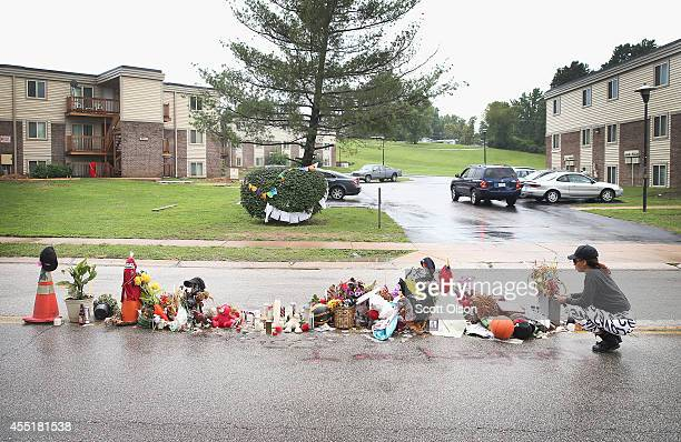 Tamika Staton leaves a personel message at a memorial which continues to grow in the middle of the road where teenager Michael Brown died after being...