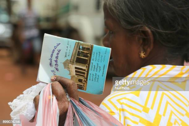 Tamil Catholic woman holding a small religious book at the Shrine of Our Lady of Madhu during the Feast of Our Lady of Madhu in Mannar Sri Lanka With...
