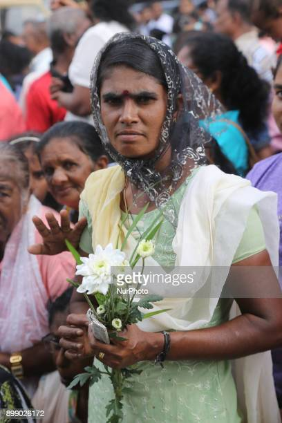 Tamil Catholic woman holds flowers as she listens to prayers being recited at the Shrine of Our Lady of Madhu during the Feast of Our Lady of Madhu...